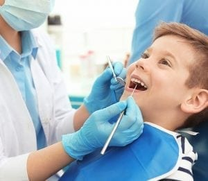Young grande prairie dental patient getting his teeth scraped