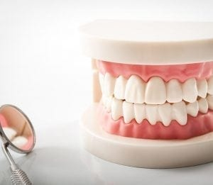 Pair of dentures next to dental mirror