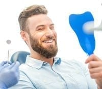 Grande Prairie dental patient smiling into mirror after getting work done on his teeth