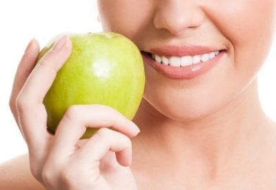 Woman holding apple next to her bright smile
