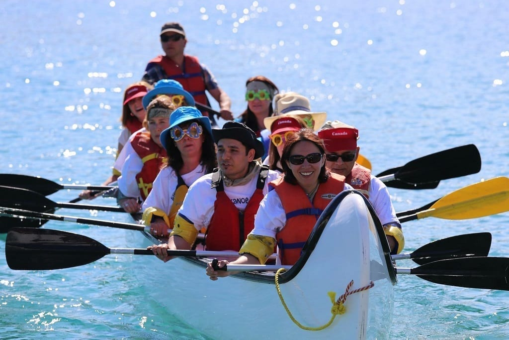 a group of people wearing funny hats and glasses with they canoe