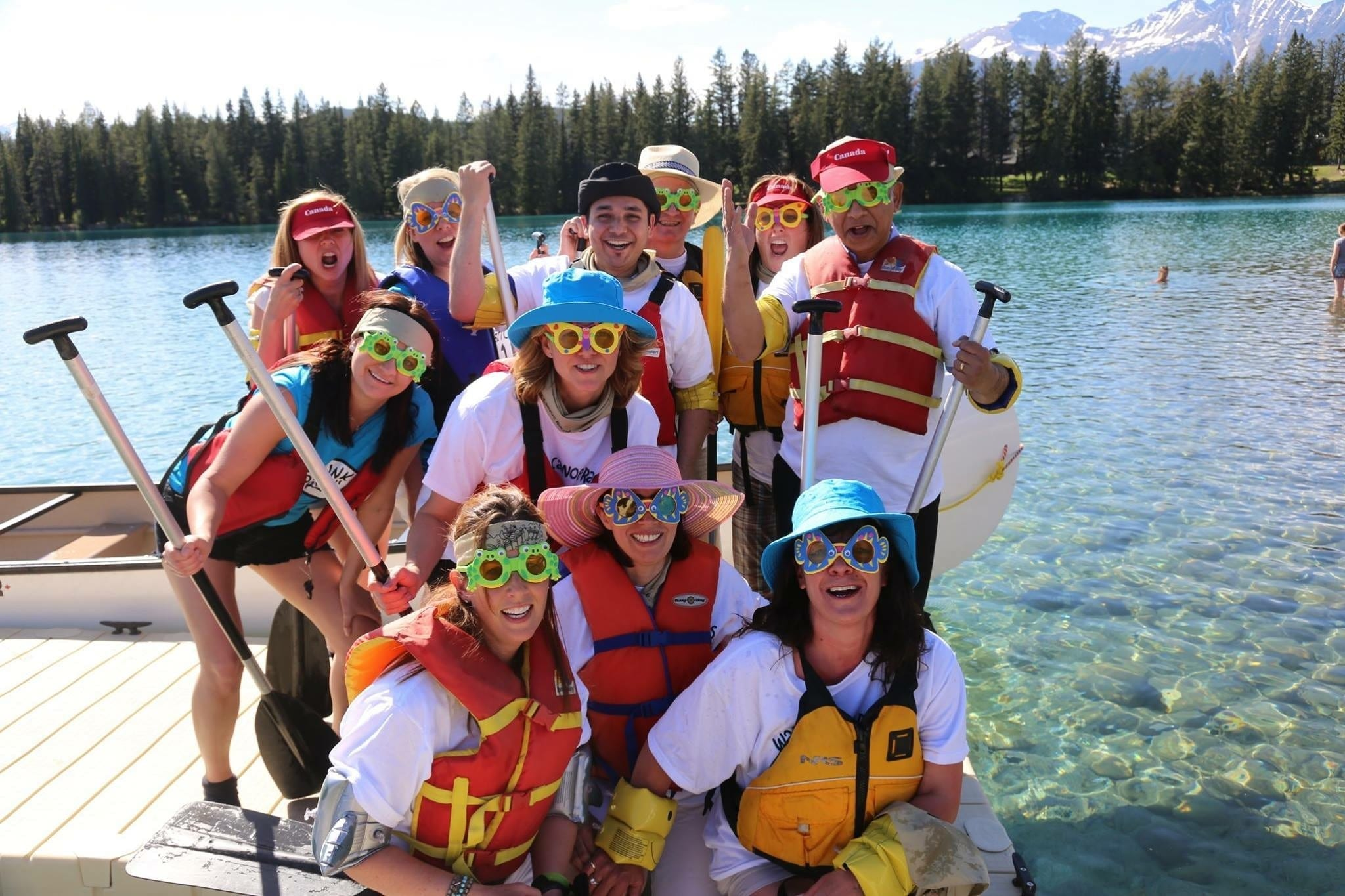 a group of people posing for the camera before they go canoeing