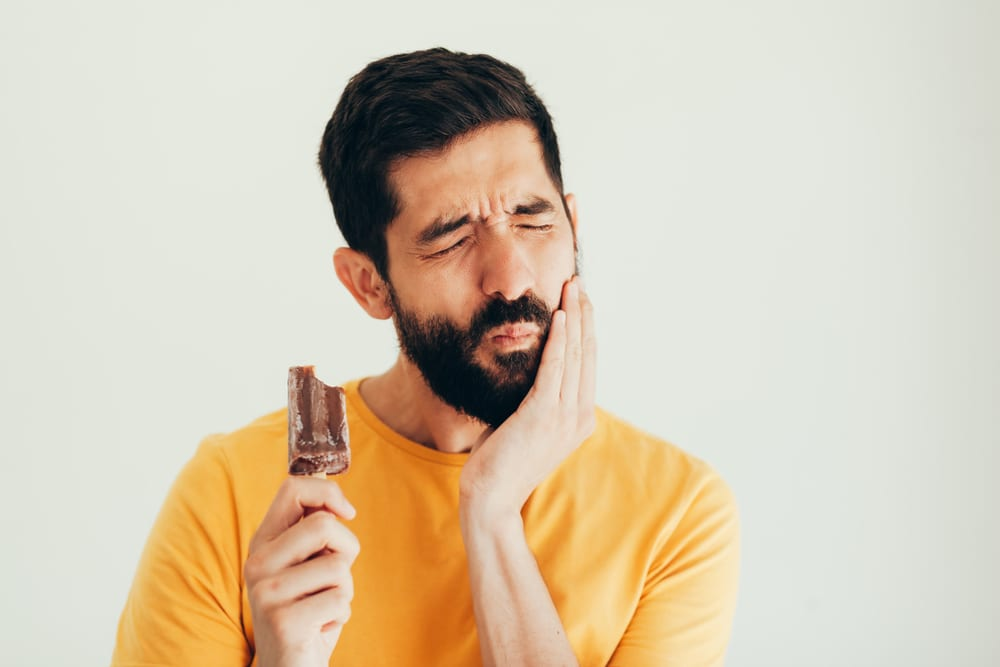 Man with Sensitive Teeth Holding a Popsicle